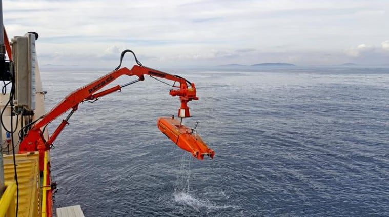 Unmanned autonomous vehicles being lowered into the ocean to survey the seabed for diamonds